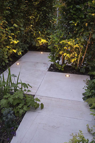 Sandstone path with uplight lighting on Laurel hedge - © GAP Photos