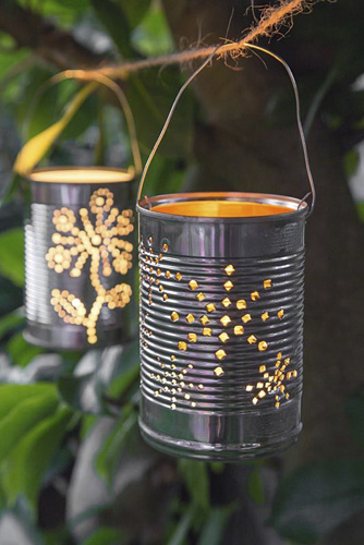 Lit tin can lanterns hanging in a tree - © GAP Photos