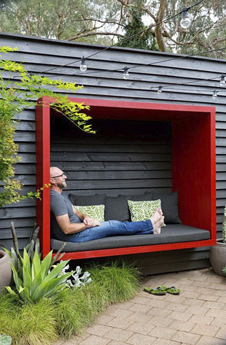 Garden owner and designer Steven Wells, relaxing in a red painted timber sitting pod he built, attached to a black painted timber wall - © GAP Photos/Brent Wilson