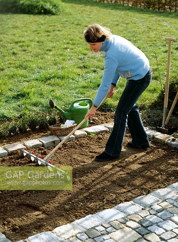 Woman marking rills for sowing in prepared soil bed