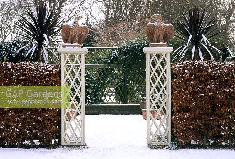 GAP Gardens Trellis pillars at entrance to garden with bird