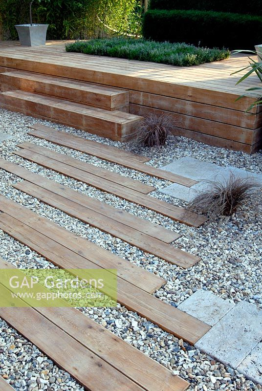 Angled Wooden Planks Paving And Gravel Leading Towards Steps To A Raised Platform