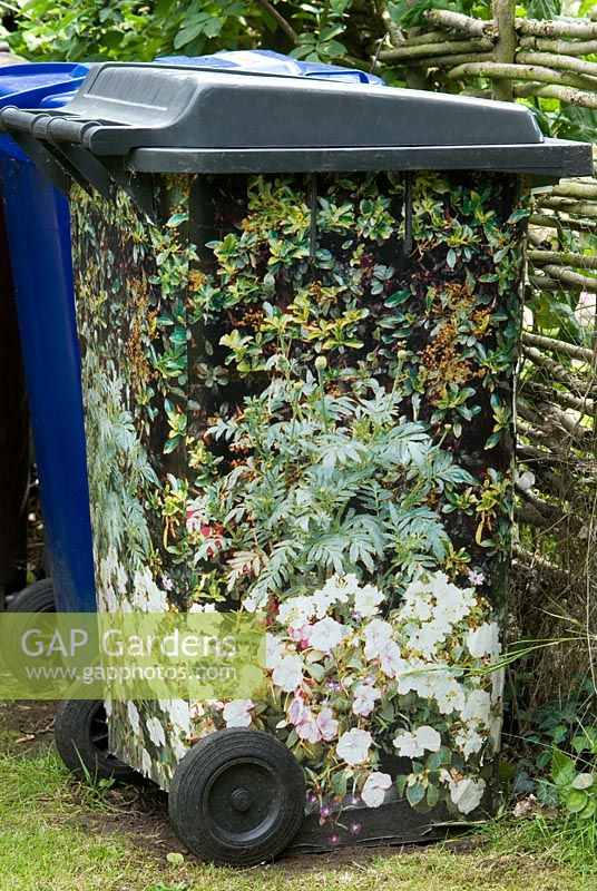 Dustbin covered in paper with a picture of flowers to disguise or camoflage the plastic bin. Lucy Redman's School of Garden Design, Rushbrook, Nr. Bury St. Edmunds, Suffolk.