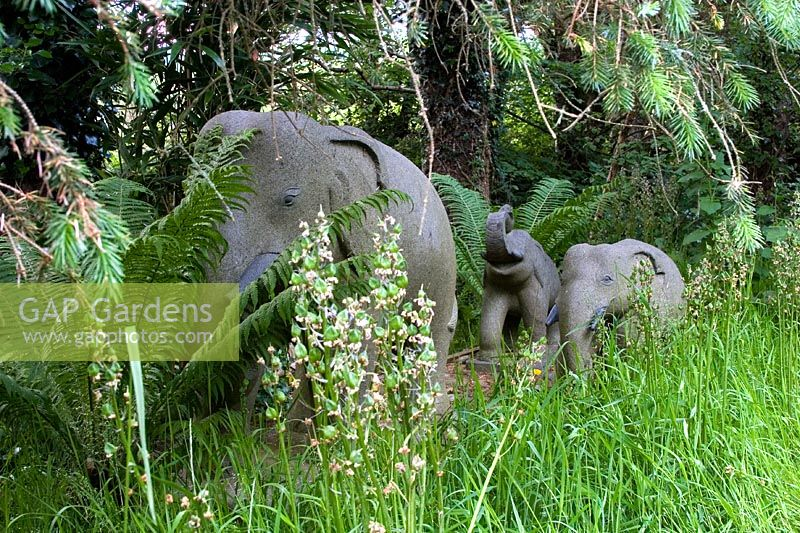 Stone Elephants As Garden Ornaments In A Woodland Setting