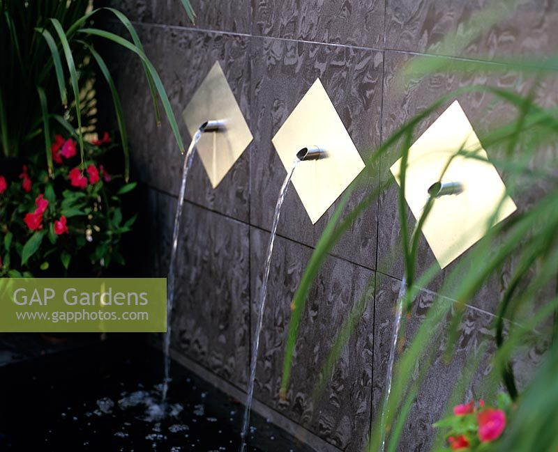 Gap Gardens Metal Water Spouts Above Pond Image No