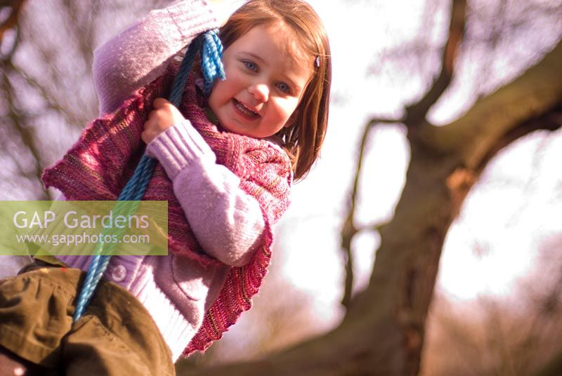 Young Girl swinging on rope tied to tree