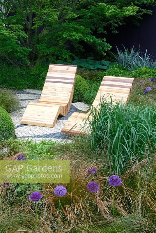 Wooden lounger seats surrounded by planting including Buxus sempervirens, Carex testacea, Euphorbia 'Whistleberry Garnet' and Allium 'Purple Sensation' in The Westland Garden, Chelsea 2007