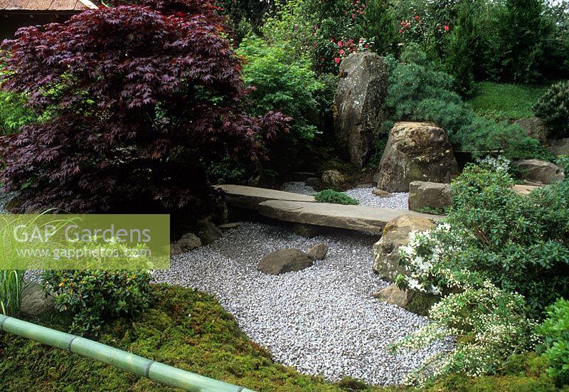 Stone Bridge Across Gravel River With Acer In Japanese Garden