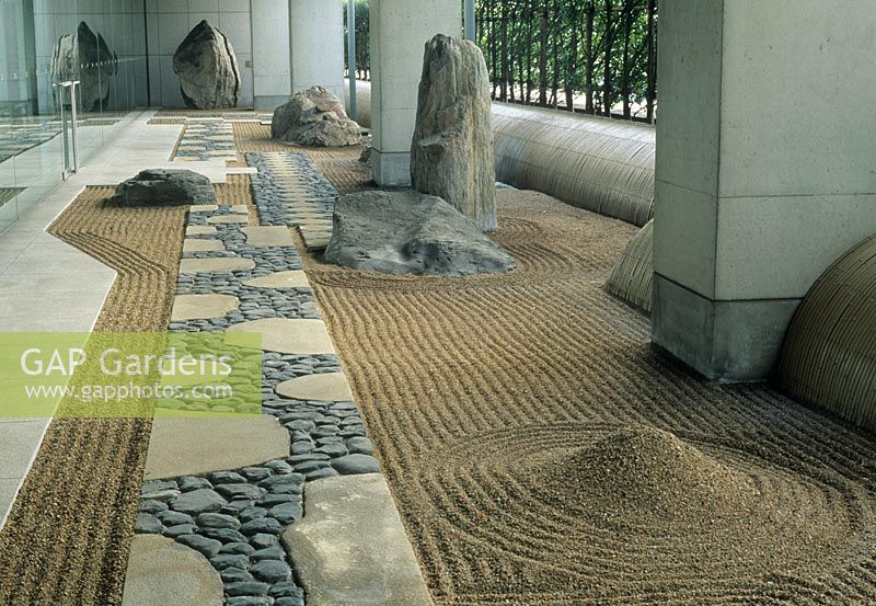 Zen style garden with rocks and raked gravel in undercroft of modern office building at The Canadian Embassy, Tokyo, Japan