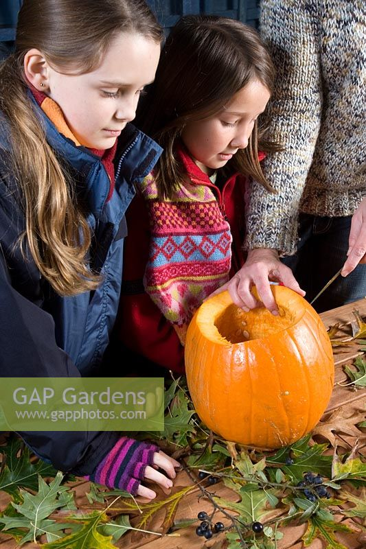 Girls watching while adult cutting face with sharp knife in pumpkin, sequence of making Halloween lantern