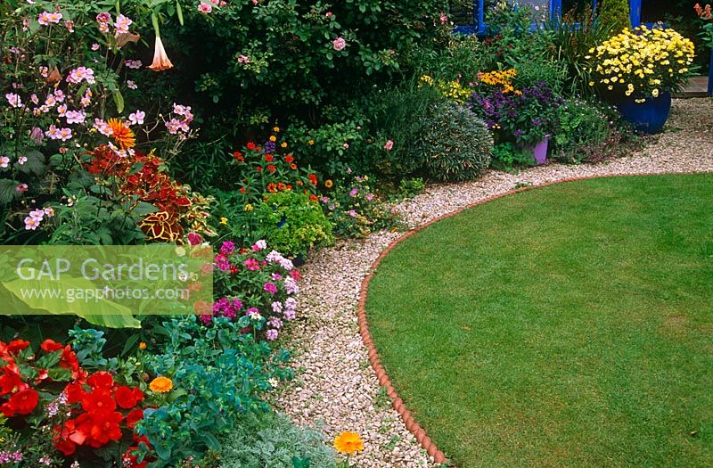 Edge Of Circular Lawn With Annuals, Half Hardey Exotics. Gravel Path And  Rope Edging