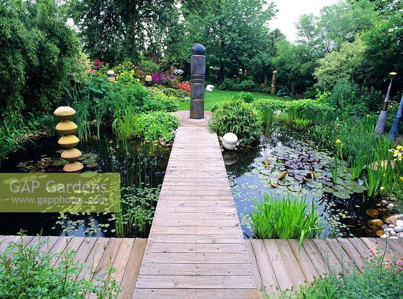 Gap gardens garden pond with decking and sculptures for Garden decking with pond