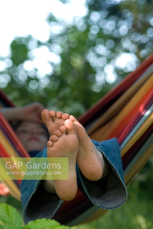 Boy relaxing in a colourful striped hammock