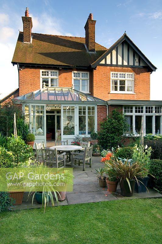 House with conservatory and patio dining area. Containers with Laurus nobilis,  Lavandula, Phormium, Lilium and Hosta - Villa Ramsdal, Chelmsford, Essex