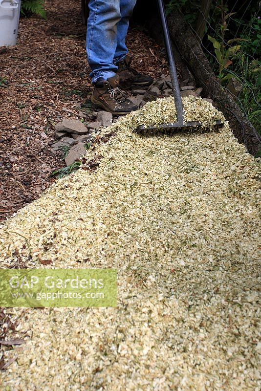 Spreading Wood Chips On Garden Path With Rake