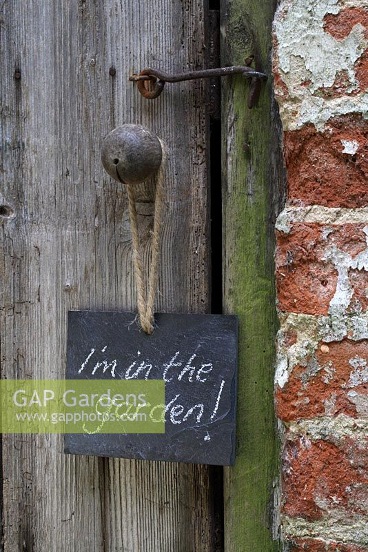 Slate sign hanging on rustic door, reading 'I'm in the garden'