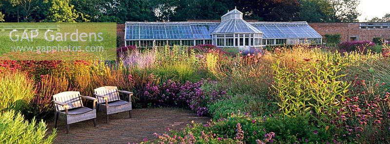 Seating area and Glasshouse in The Perennial Meadow at Scampston Hall designed by Piet Oudolf
