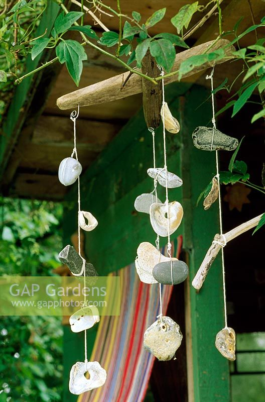 Windchime, offcuts from an old garden hammock and a nesting box help to conceal a hideaway in garden
