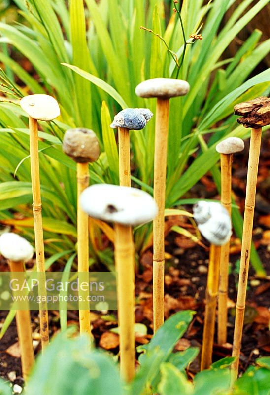Shells, stones and driftwood on top of bamboo canes