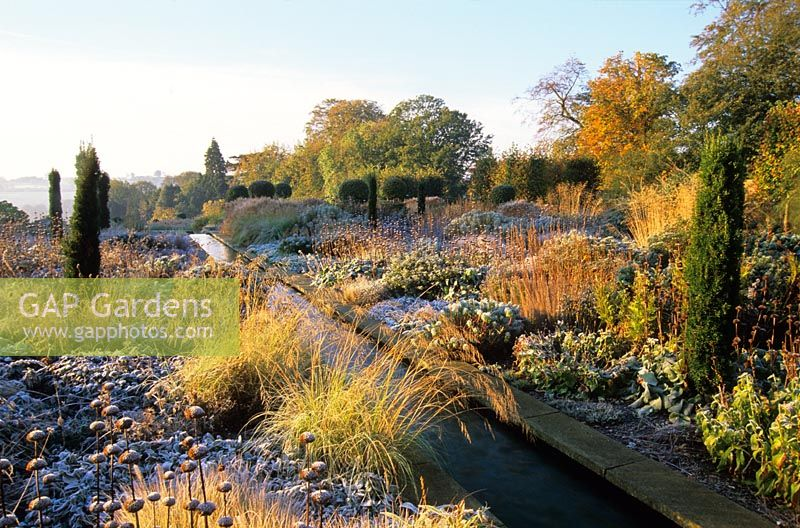 A water rill with frost on perennials and ornamental grasses at Broughton Grange, Oxfordshire