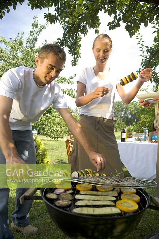 Couple cooking vegetable kebabs on barbecue in garden