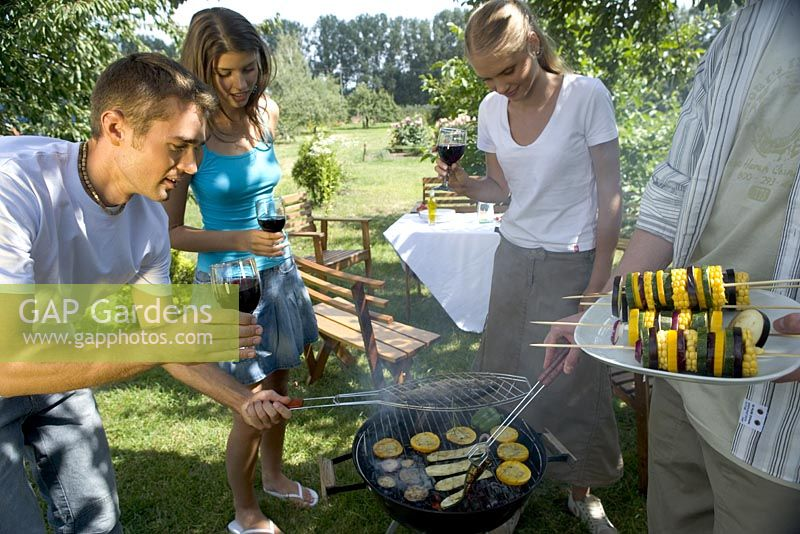 Couples cooking fish and vegetable kebabs on barbecue in garden