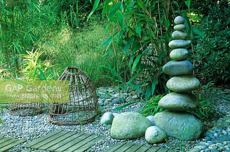 Sculptural tower of large pebbles with wooden panels inset in to a pebble path in a seaside style garden with grasses and bamboos - Designed by Alan Titchmarsh at Barleywood, Hampshire