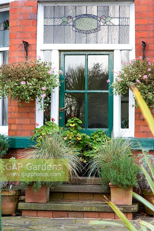 Green Back Door To A Traditional Victorian Red Brick House With Stained  Glass Surround. Raised
