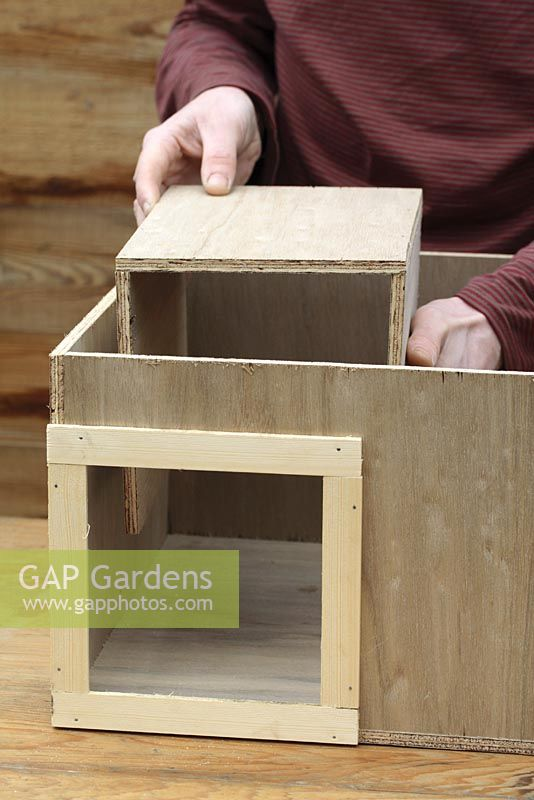 Step by step 5 of making a hedgehog house - Placing entrance tunnel, also made from plywood into wooden box