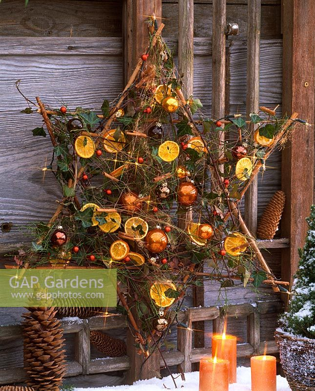 star made from sticks decorated with hedera vaccinium dried orange slices and christmas tree