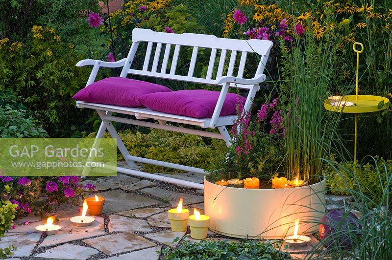 White wooden bench with pink cushions on patio with lit candles, water feature and planting of Lythrum and Scirpus