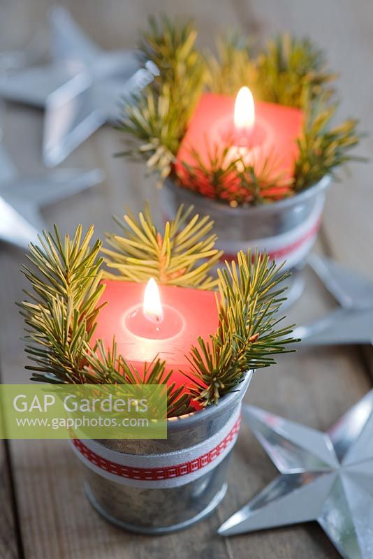 Red candles in mini zinc buckets with fir tree foliage and ribbon as a table decoration.