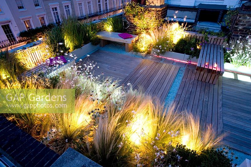 Gap Gardens Decked Terrace At Night With Pink And White Led Lighting And Blue Glass Gravel