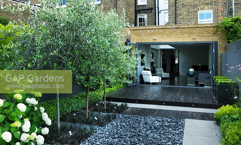 Gap gardens small contemporary garden with black stained for Grey decking garden ideas