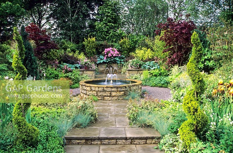 Formal Water Garden With Raised Circular Pond And Fountain On Patio On  Sloping Site With Mixed