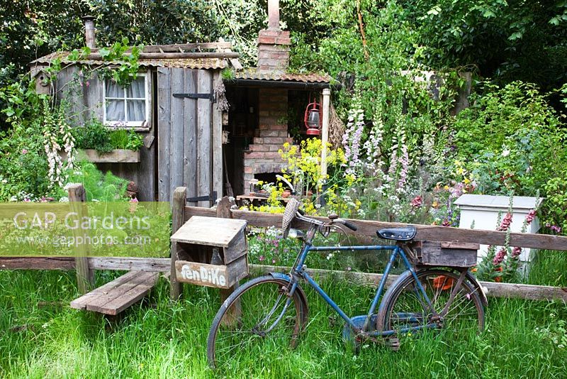 A wooden stile leads into The Fenland Alchemist Garden, sponsored by Giles Landscapes - Gold medal winner for Best Courtyard Garden at RHS Chelsea Flower Show 2009