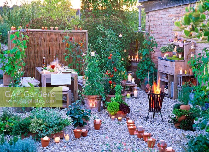 Dining area and gravel pathway lit with candles, container plants include vegetables, herbs and Lathyrus