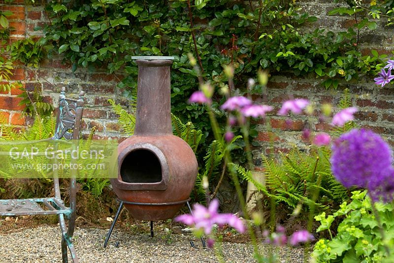 Chiminea in English country garden, with ferns and brick wall