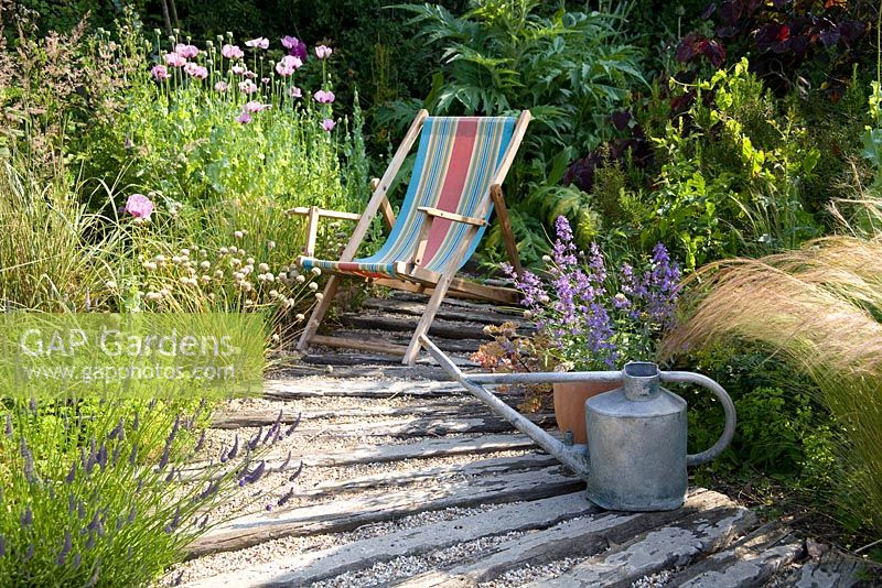 Deck chair in coastal-look garden, with watering can and container with Nepeta
