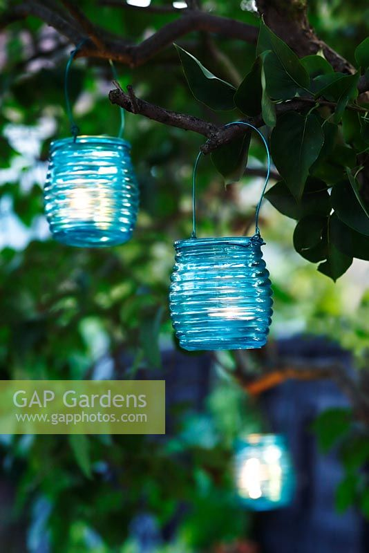 Turquoise glass tealight holders hanging in tree