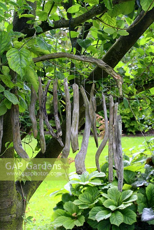 Driftwood wind chimes hanging from apple tree