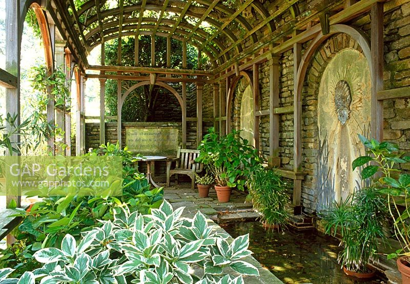 Hostas and tender plants benefit from the shelter of the Arbour Terrace that also has a pond and decorative fountain. Dumbarton Oaks, Washington USA