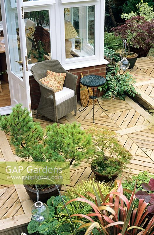 Sophisticated timber deck made with individual deck squares laid to form a diamond pattern around a newly installed conservatory