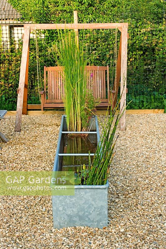 Gap gardens gravel garden with metal pond and swing seat for Garden pond gravel