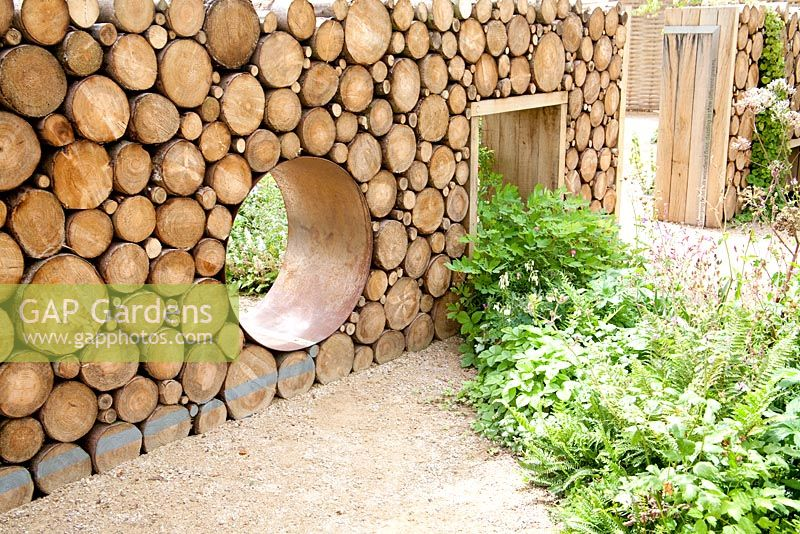 'Narratives of Nature' garden with reclaimed log wall and moon gate. Planting includes ferns, Geranium sylvaticum, Luzula nivea, Atriplex hortensis, Umbilicus rupestris and Betula pubescens. Future gardens, St Albans, Herts