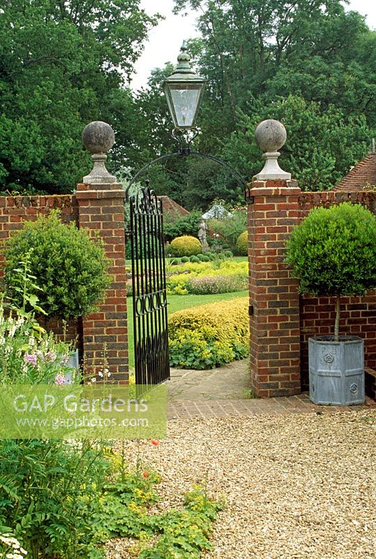 High Garden Wall With Brick Pillars, Topped With Stone Balls, Standard Box  Trees In Lead Planters On Either Side. Open Gate Leading To Well Tended  Lawn Area ...