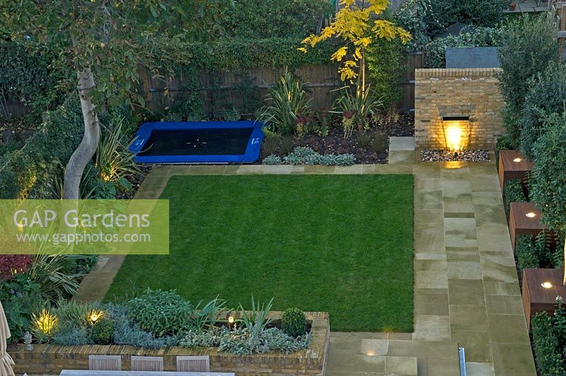Contemporary Urban Garden With Lighting, Lawn, Raised Brick Border, Water  Feature And Play
