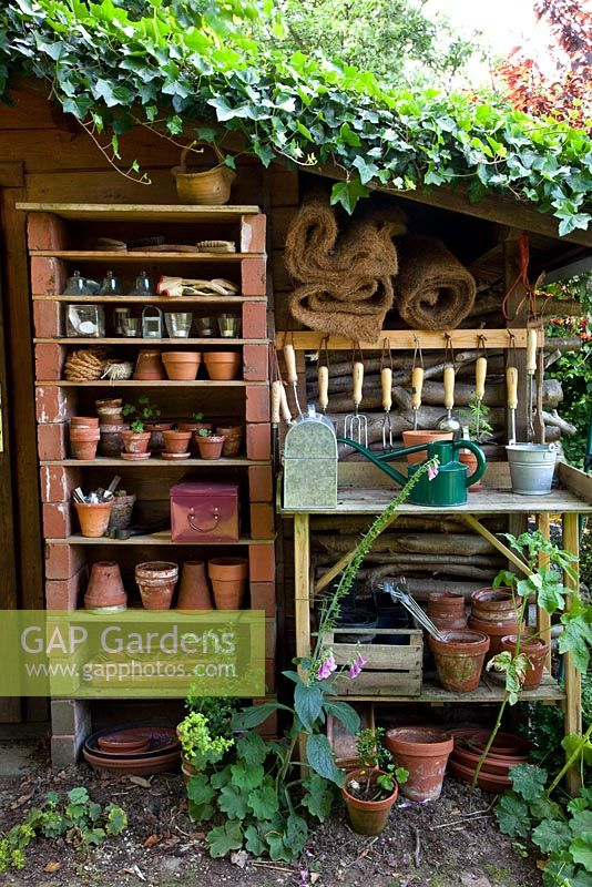 Garden Shed With Shelves Of Terracotta Pots And Gardening Tools.