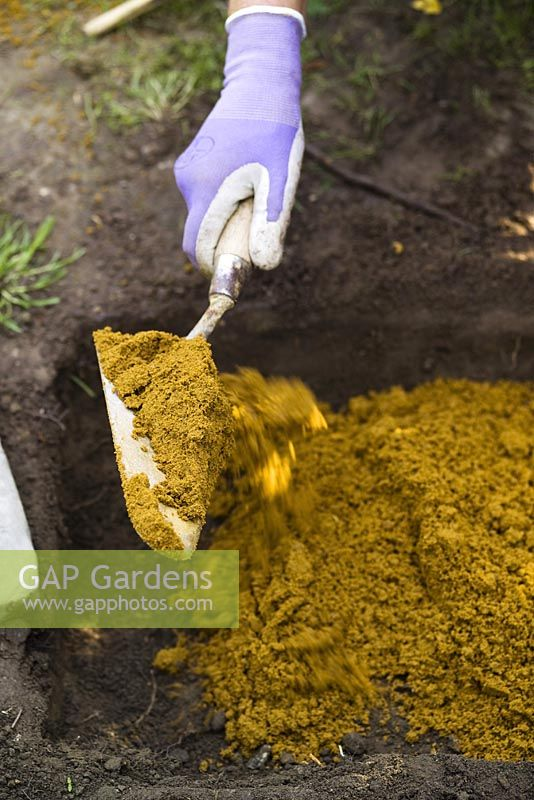 Adding sharp sand to dug out soil before laying a paving slab