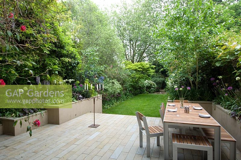 Large urban garden with furniture on patio. The Merrick Garden, London, UK